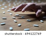 Small photo of Drug addict with withdrawal symptoms reaching out to many pills on the floor with hand. Drug addiction, medical abuse and narcotics hook and dependence concept. Tablet overdose.