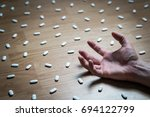 Small photo of Drug addiction, medical abuse and narcotics hook and dependence concept. Drug addict with withdrawal symptoms lying on floor. Tablet overdose. Depression and problem. Hand surrounded by many pills.