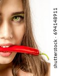 Small photo of Portrait of a girl brown, green eyes. Holds chili in the mouth. Advertising spices, hot pepper. Acute, commonly used as a spice or seasoning for the taste of food.