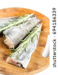 Small photo of Fresh raw hake fish with rosemary branches on the round wooden board.