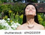 woman in flower garden | Shutterstock . vector #694203559