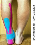 Small photo of Legs of a man looking at the calves and achilles tendon. The foot with a wound covered with tape used in elastic therapeutic tape (Kinesio Taping).