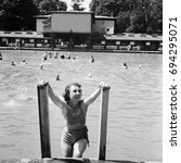 Small photo of Smiling woman climbing out of swimming pool