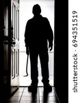 Small photo of Intruder standing at doorway threshold, in silhouette with crowbar