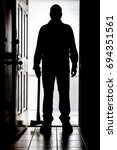 Small photo of Intruder standing at doorway threshold, in silhouette with axe