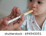 parent feed the medicine to 1... | Shutterstock . vector #694543351
