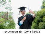 happy a man in his graduation... | Shutterstock . vector #694545415