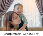 happy asian mother and son on... | Shutterstock . vector #694551679