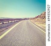 winding asphalt road in the... | Shutterstock . vector #694552927