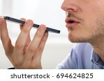 Small photo of Close-up Of A Businessman Using Voice Assistant On Mobile Phone