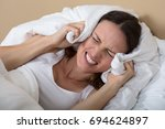 troubled woman in bed covering... | Shutterstock . vector #694624897