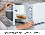 woman's hands closing microwave ... | Shutterstock . vector #694624951