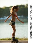 Small photo of BELGRADE, SERBIA - 21. AUGUST 2011. Unidentified beautiful and attractive girl in bikini swimwear and jeans shorts drives roller skate around the Ada Ciganlija lake. Belgrade known for beautiful girls