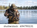 Small photo of Bearded soldier of special forces in action during river raid in the jungle terrain. He is waist deep in the water and mud and ready to meet enemy, survive and fight in agressive hostile environment
