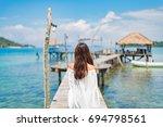 a girl walking on the bridge to ... | Shutterstock . vector #694798561