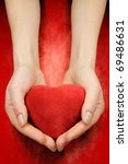 hands with heart on red grunge background - stock photo