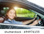 woman smiling at camera in car.... | Shutterstock . vector #694976155