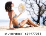 sexy girl with a hat sunbathing ... | Shutterstock . vector #694977055