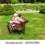 Little boy and girl in park on a bench - stock photo