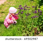 Little girl smells the wild flowers - stock photo