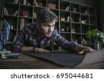 young man sitting at wooden... | Shutterstock . vector #695044681