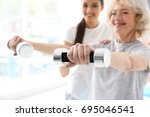 physiotherapist working with... | Shutterstock . vector #695046541