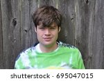 Small photo of Young Adult Male with Autism relaxing against an old wooden fence in the background