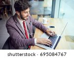young handsome man working on... | Shutterstock . vector #695084767
