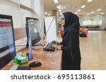 arabic woman typing on computer ... | Shutterstock . vector #695113861