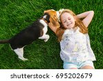 Stock photo cute little girl is playing with her dog in the green park 695202679