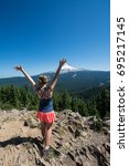 """Small photo of An adult female hiker on the summit of """"Tom Dick and Harry Mountain"""" in the Mount Hood National Forest, raises her arms in accomplishment"""