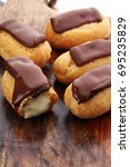 Small photo of Traditional French dessert. Eclair with chocolate icing. Pastery concept