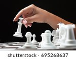 woman plays chess  holds a... | Shutterstock . vector #695268637