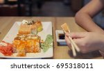 girl eating sushi and dip in... | Shutterstock . vector #695318011