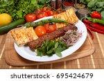 adana kebab is a long  hand... | Shutterstock . vector #695424679