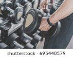 man hand taking iron dumbbells... | Shutterstock . vector #695440579