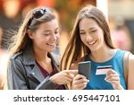 two happy friends buying on... | Shutterstock . vector #695447101