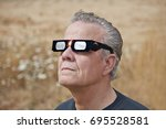 man viewing solar eclipse with... | Shutterstock . vector #695528581