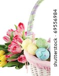 Easter basket and eggs near a bouquet of tulips over a white background. Shallow DOF. - stock photo