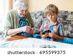 Small photo of Active little preschool kid boy and grand grandmother playing card game together at home. little child and retired woman having fun. Happy family: grandchild and senior woman