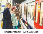 people waiting for the train at ... | Shutterstock . vector #695631085