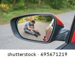 Small photo of Hit and run concept. View on injured man on road in rear mirror of a car.