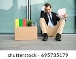 fired businessman reading the... | Shutterstock . vector #695735179