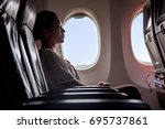 woman sitting in a flying... | Shutterstock . vector #695737861