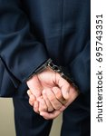 Small photo of arrested businessman in handcuffs. Businessman bribetaker or briber. Concept of fraud, detention, crime and bribery