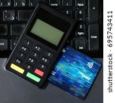 Small photo of close-up bank card and payment device lying on keyboard, top view. Concept of internet crime, hacking, cyber crimes and virtual payments