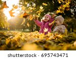 siblings playing with maple... | Shutterstock . vector #695743471