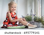 the smiling girl sits at a... | Shutterstock . vector #695779141