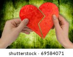 love and divorce. two hands holding broken heart - stock photo
