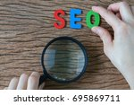 Small photo of Female hands holding magnifying glass and arrange colorful alphabets abbreviation SEO